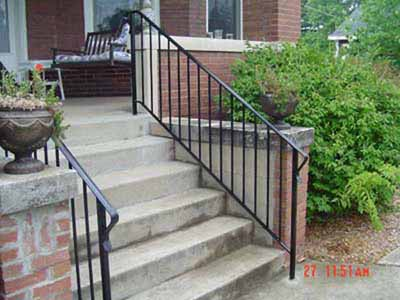 Metal stair rail inside existing concrete porch wing wall